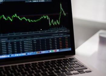 Computadora con gráfico de acciones de mercados financieros.