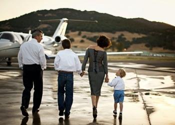 Familia caminando hacia un jet privado tomados de la mano.