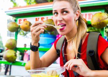 Mujer europea comiendo en un puesto de cocina móvil en un viaje de Yakarta explorando la comida de la calle Indonesia