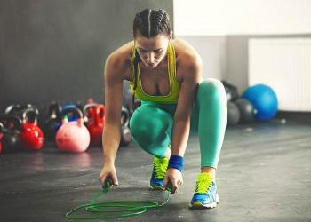Una mujer joven y en forma está saltando a la cuerda.