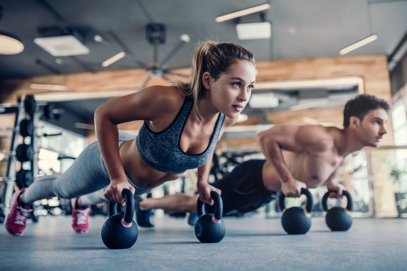 Pareja joven haciendo ejercicios en el gimnasio