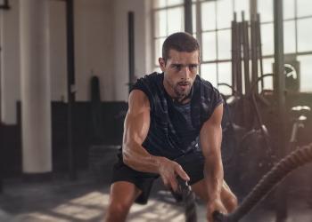 Hombre atlético haciendo ejercicios con la cuerda.