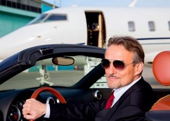 Hombre de negocios en un descapotable frente a su jet privado corporativo