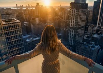 Mujer rica disfrutando del atardecer desde el balcón de un apartamentos de lujo en la ciudad de Nueva York.