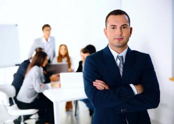 Hombre de negocios de pie delante de una reunión de trabajo
