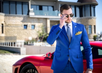 Hombre en traje a medida con gafas posando frente a casa y coche caro