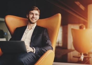 Joven empresario exitoso en la oficina de negocios sentado en un sillón naranja con ordenador portátil.