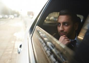 Millonario mirando por la ventana del coche mientras viaja por la ciudad