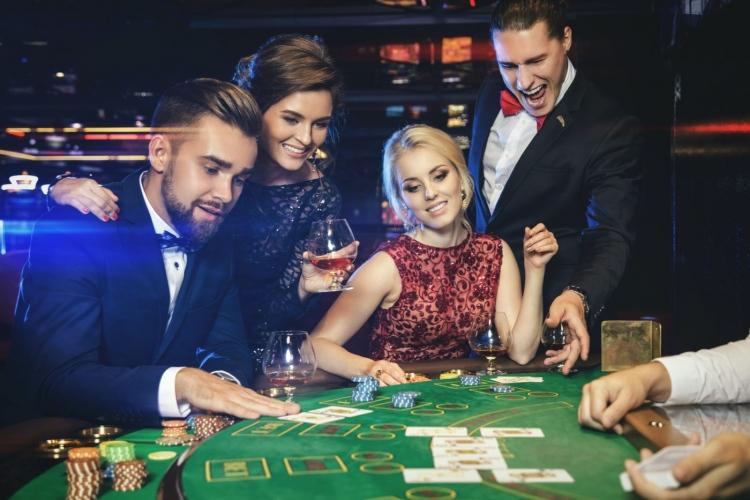 Grupo de jóvenes ricos jugando al póker en el casino
