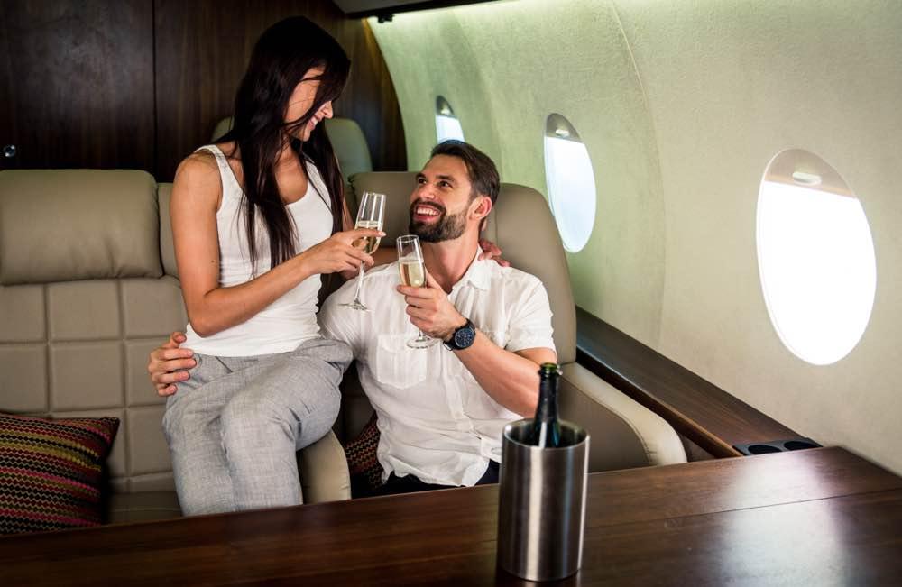 Pareja millonaria viajando en un jet privado de lujo