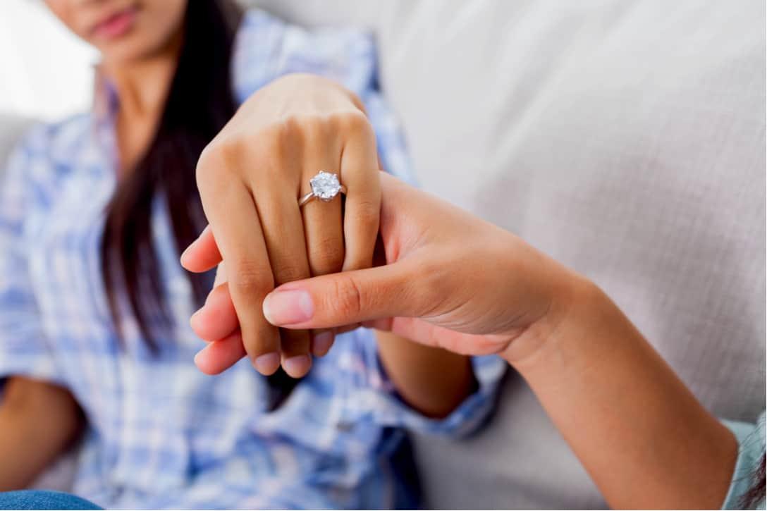 Anillo de compromiso de diamante en la mano de una mujer sostenida por su prometido.