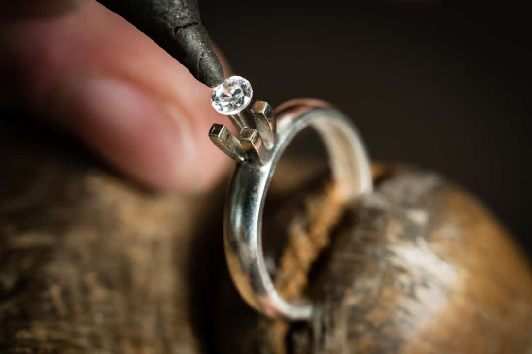 Poniendo el diamante en un anillo compromiso.