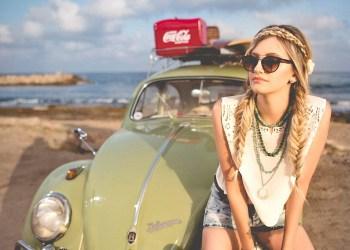 Muchacha en la playa en un VW