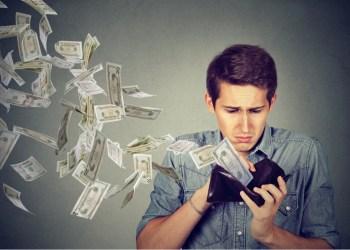 Hombre triste mirando volar de su billetera miles dólares
