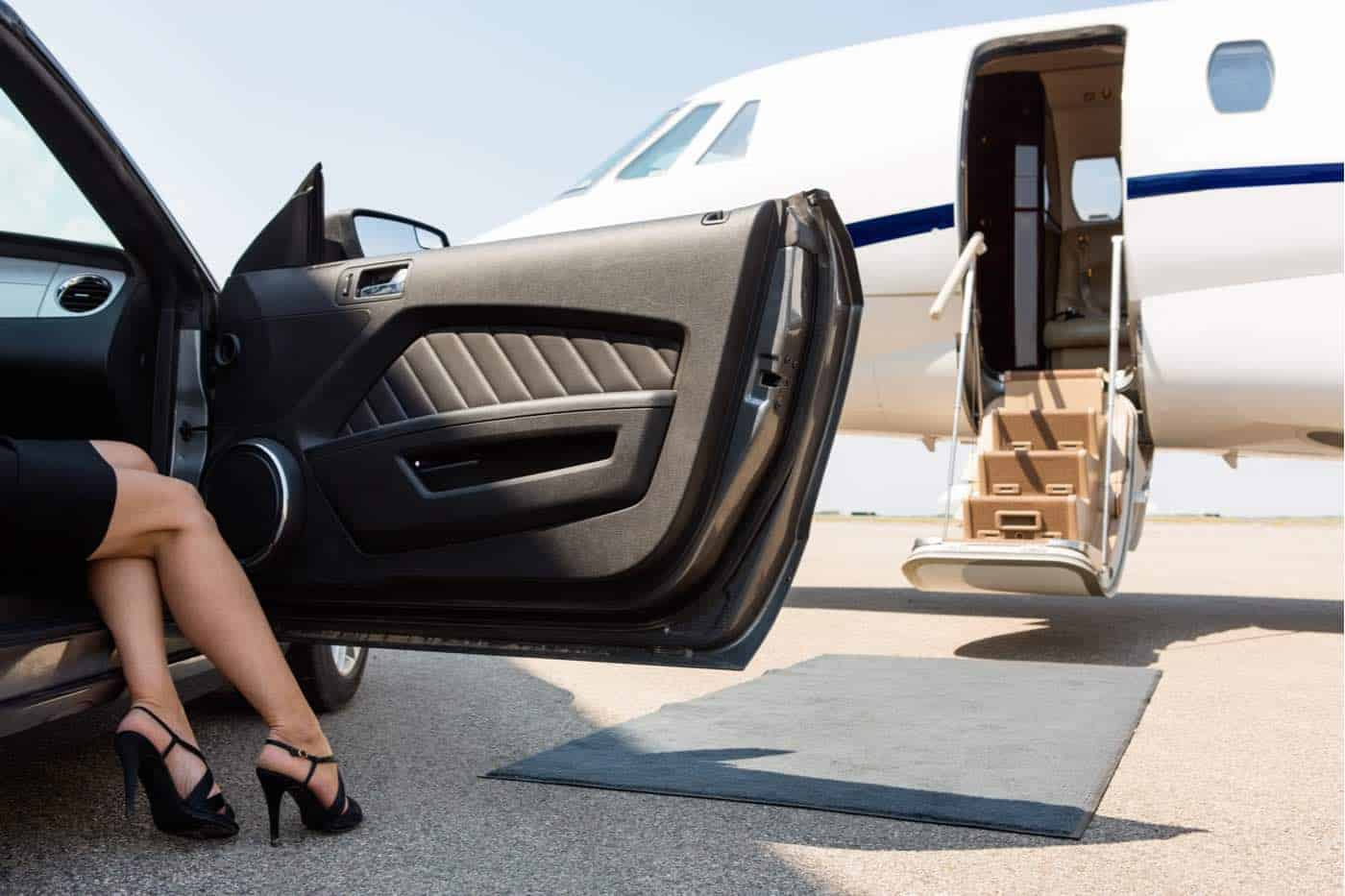 Mujer rica saliendo del automóvil frente a un avión privado