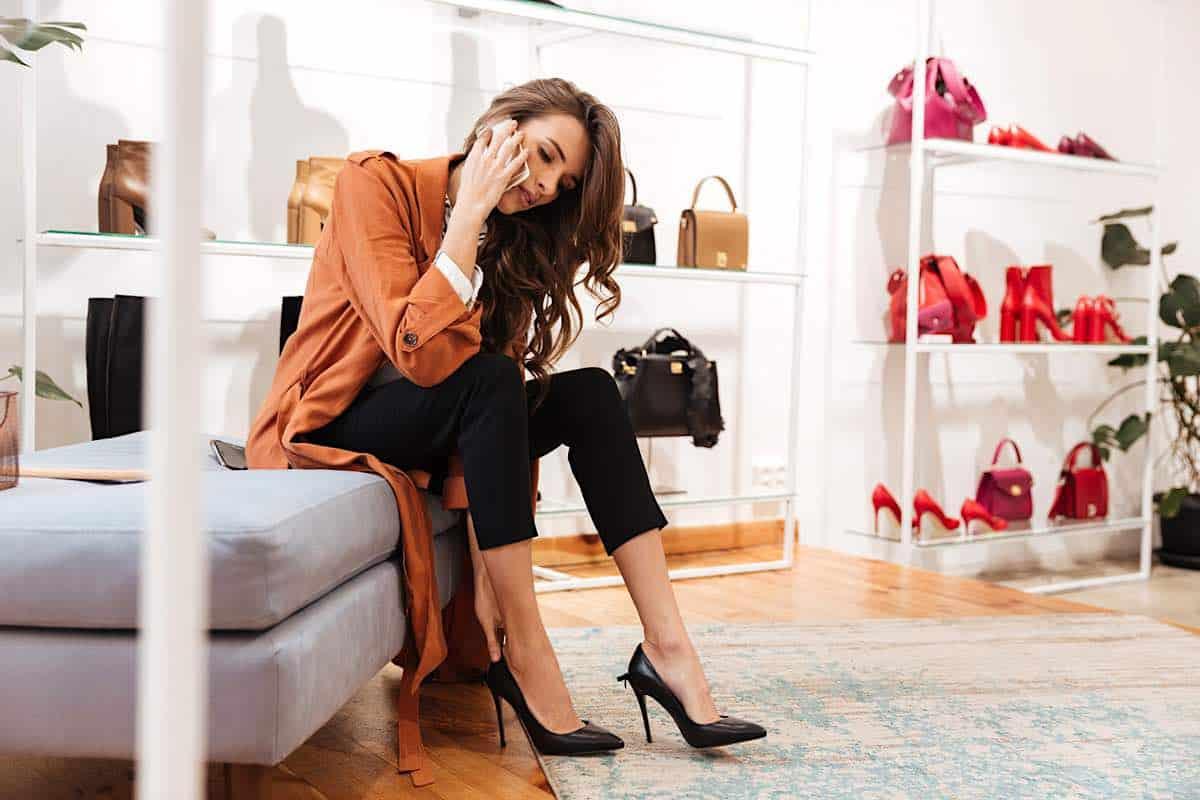 Mujer probándose zapatos mientras habla por teléfono móvil en una zapatería