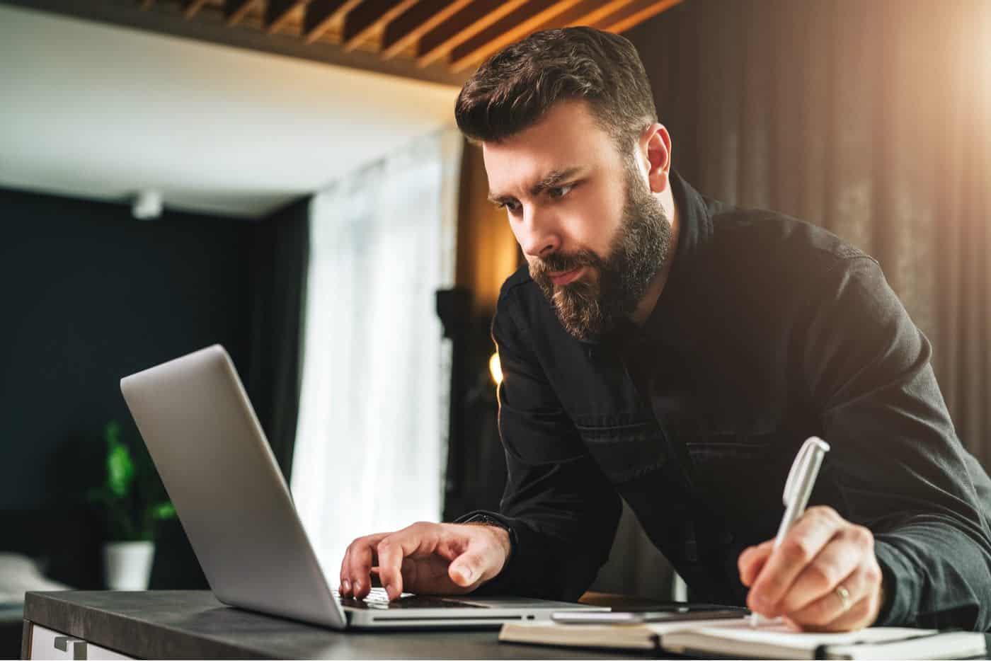 Empresario con barba con su computadora