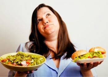 Mujer gorda eligiendo entre una hamburguesa y ensalada