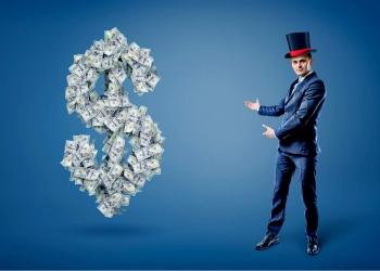 Empresario con sombrero de mago frente a un gran signo de dólar hecho de billetes.