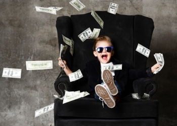 Niño rico sentado en un sillón y tirando dinero efectivo en dólares