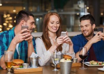 Amigos con teléfonos inteligentes cenando en un restaurante