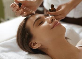 Cosmetóloga aplicando aceite en la cara de una juven en el Centro de cosmetología.
