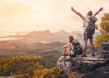 Excursionistas mochileros relajándose en la cima de una montaña, disfrutando del atardecer.