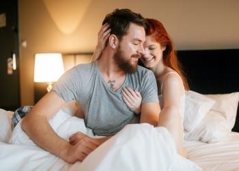 Mujer abraza a un hombre en la cama