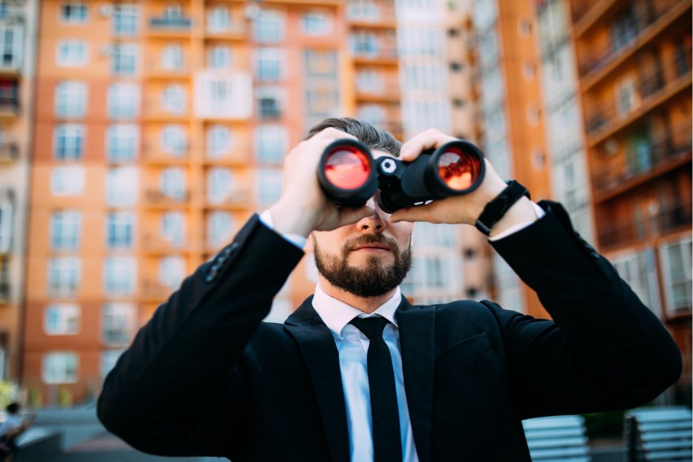 Hombre de negocios con binoculares espiando a los competidores