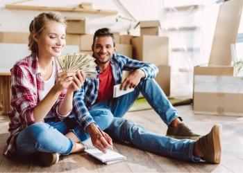 Joven pareja feliz con calculadora y billetes de dólares contando dinero en casa nueva.