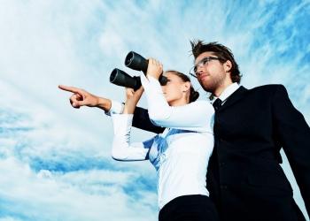Exitosa mujer y hombre de negocios mirando a través de un binocular