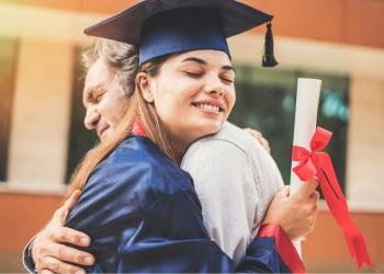 Estudiante graduada de la universidad abrazando a su padre