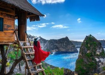 Muchacha en una casa en árbol en la playa de Atuh en la isla de Nusa Penida, Bali en Indonesia.