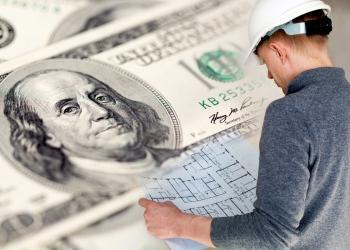 Ingeniero con rollos de planos y dólares