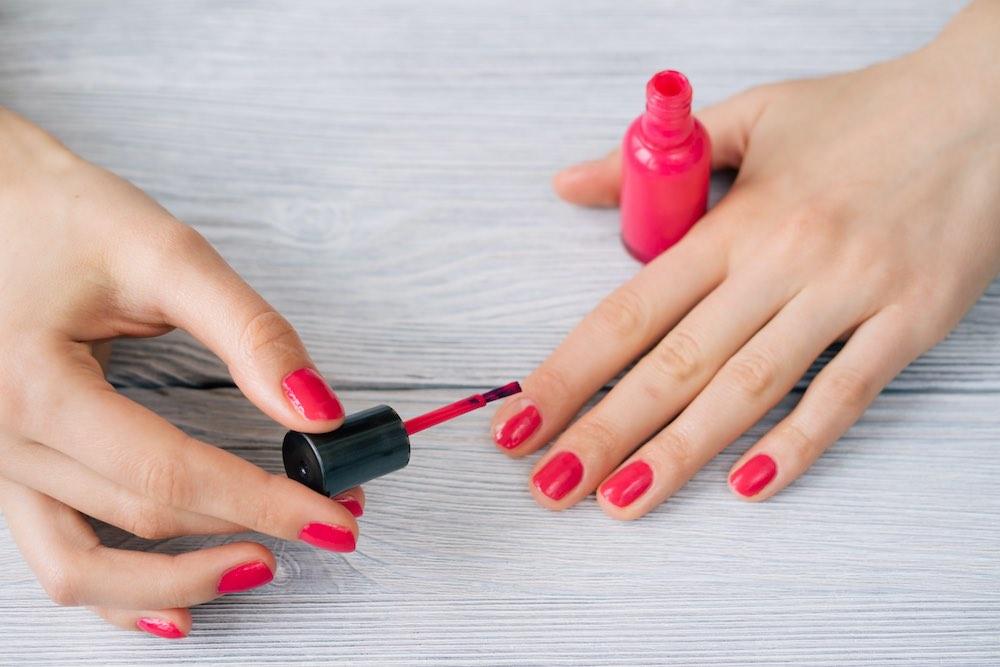 Mujer pintando sus uñas con laca roja