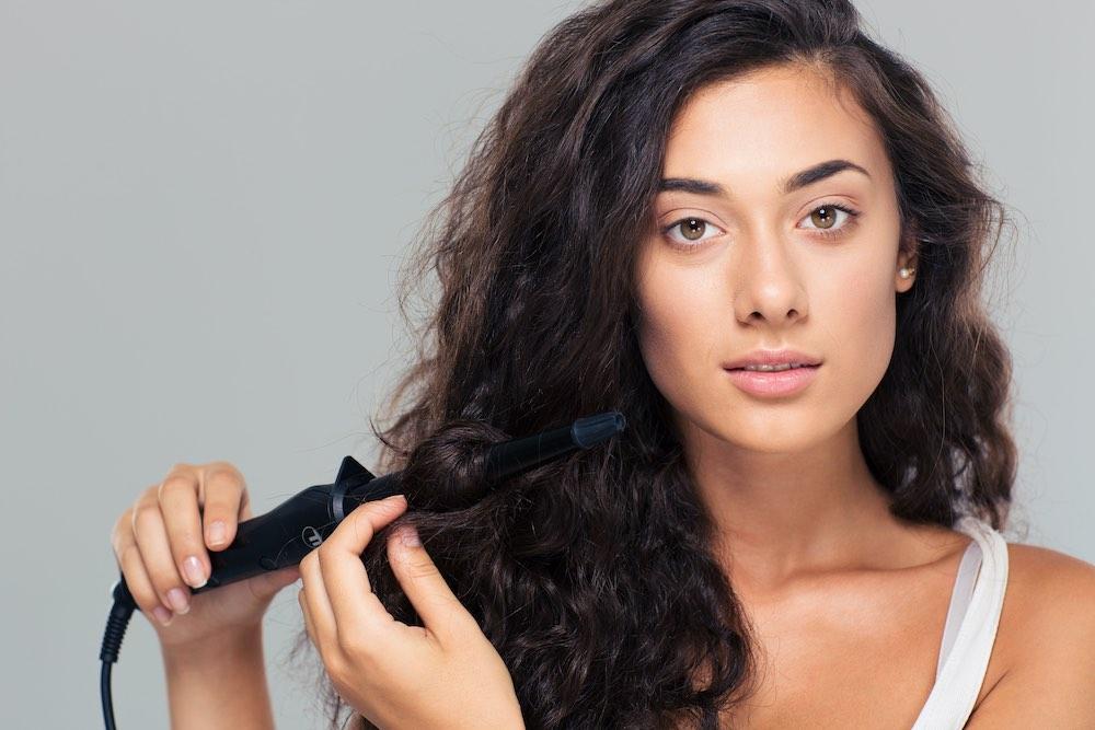 Mujer peinándose con una plancha de pelo