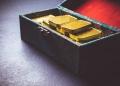 Barras de oro puro en una maleta.