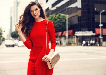 Hermosa mujer con un vestido rojo y bolso de oro, caminando por la calle.