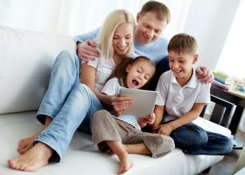 familia feliz con dos niños sentados en el sofá.