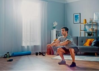 Hombre atlético haciendo ejercicios de sentadillas en casa