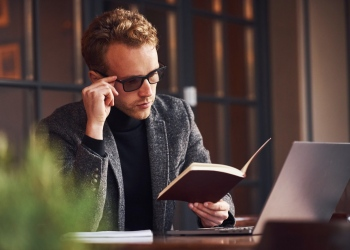 Joven empresario se sienta en la cafetería con su computadora portátil y lee un libro
