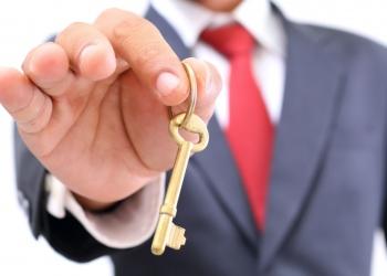 Empresario mostrando la llave de oro para el éxito