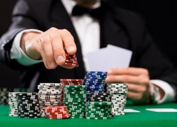 Jugador de póker con naipes y fichas en la mesa de casino.