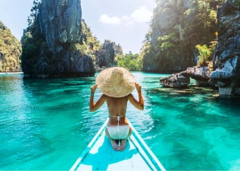 Mujer en un barco y mirando hacia la laguna de El Nido, Palawan, Filipinas.