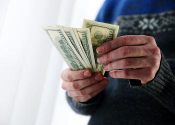Hombre sujetando dólares estadounidenses en efectivo