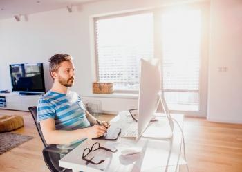 Hombre sentado en el escritorio trabajando desde casa en la computadora, usando una tableta.