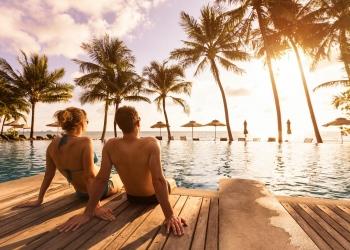 Pareja disfrutando de vacaciones en la piscina de un playa resort tropical.
