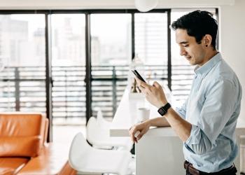 Empresario asiático con audífono usando su teléfono móvil.
