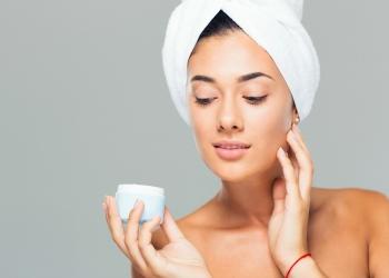 Mujer con toalla en la cabeza con tarro de crema