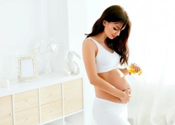 Mujer embarazada aplicando aceite en el vientre